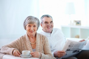 smiling-couple-drinking-coffee-and-reading-the-newspaper_1098-1168