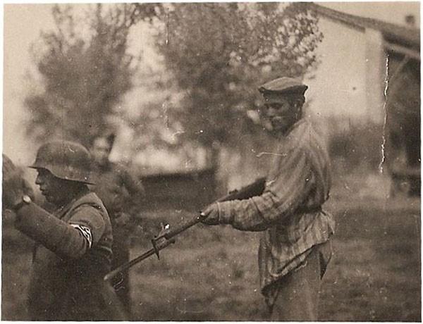 38. A liberated Jew holds a Nazi guard at gunpoint