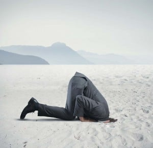 Ostrich-denial-change-motivation-head-in-the-sand-business-man-hide-fear-challenge