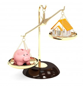 18540769 - piggy bank and house on bowls of scales. isolated over white