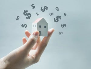 House Model On Human Hands With Dollar Icon.