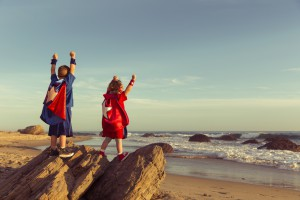 Boy And Girl Dressed As Superheroes On California Beach