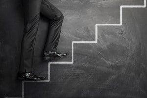 Businessman Climbing The Career Steps Drawn On A Black Chalkboar