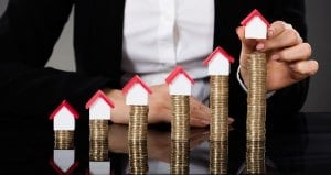 Businesswoman Arranging House Model On Stacked Coins