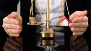 Balancing Money And House On Scales Of Justice