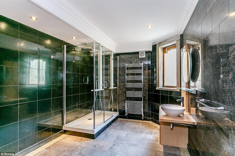 There is a large Jacuzzi shower with coloured polished granite walls and flooring