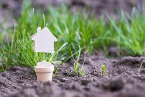 House Model Toy Miniature On Grass Blurred Background. Real Estate, Rent, Sale Or Buying Property Concept