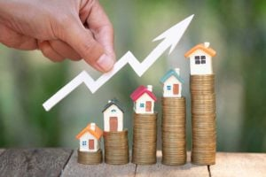 Concept Of Property Real Estate Investment With Houses Placed On Top Of Coins